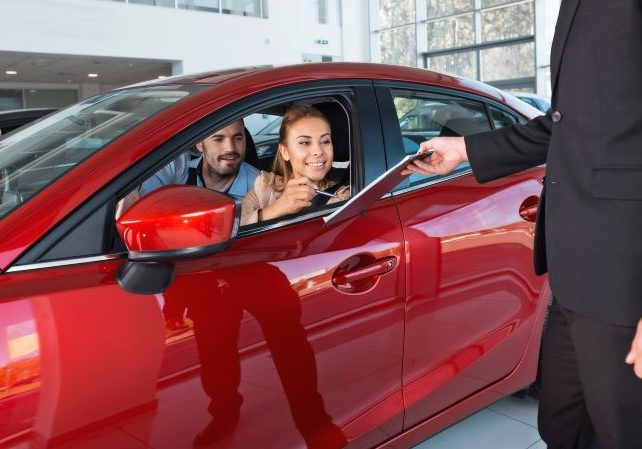 Photo of young couple sitting inside new car. Woman signing contract. Concept for car rental